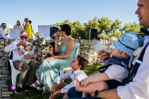 A baby sips from his bottle while the adults enjoy champagne and beer in Puglia in this photo composed by a Calabria wedding photographer.