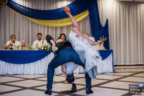 The groom flips the bride over his shoulder on the dance floor in NDK in this photo created by a Sofia, Bulgaria wedding photographer.
