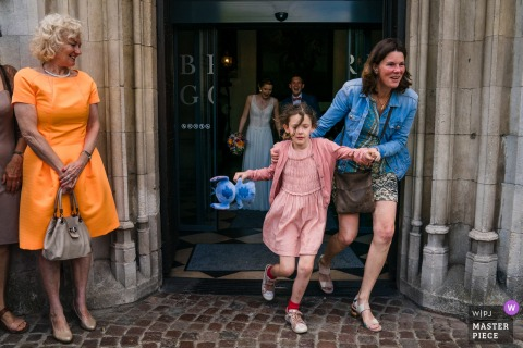 A little girl and her mother run out of the Brugge Town Hall in La Petite Fabriek in this wedding photo by a Flanders photographer.