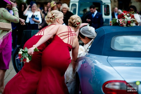 The Farm, Cambridgeshire, UK Bridesmaids helping the bride out of the car - Wedding Reportage