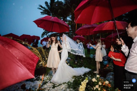 Ritz-Carlton, Krabi, Thailand Wedding ceremony photography in a rainstorm with red umbrellas