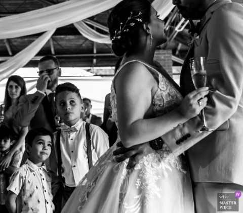 Guests watch as the bride and groom dance in Caracas holding champagne in this black and white documentary wedding photo captured by a Miranda, Venezuela photographer.