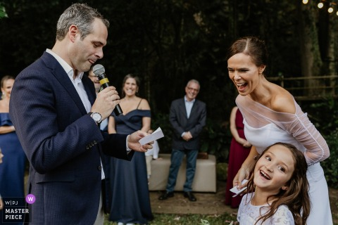 The bride and a little girl laugh as a man gives a speech during this wedding at Casa dos Novios by a Porto Alegre award-winning photographer.