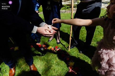 Jackson, New Hampshire Wedding ceremony photography | The flower girl hands the groom the rings under the chuppah