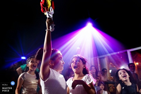A young girl scoffs as another holds the bride's bouquet in the air at Bella Eventos in this wedding photo by a Goias, Brazil photographer.
