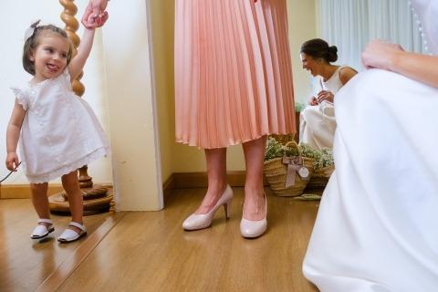 Une femme tient la main d'une petite fille pendant que la mariée s'agenouille et lui sourit avant la cérémonie dans cette photo de mariage | Photographie d'enfants à des mariages.