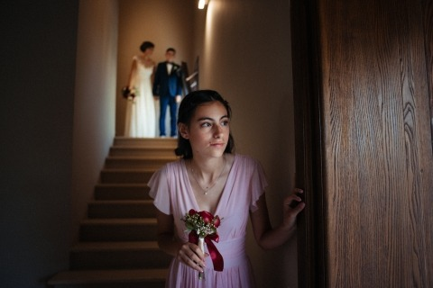 La photographe de mariage capte un moment précieux alors que la demoiselle d'honneur regarde timidement avant d'entrer