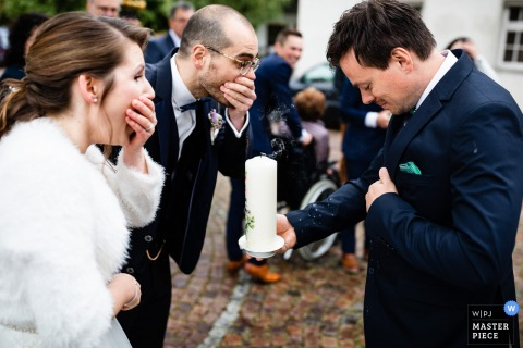 The bride and groom cover their mouths in surprise realizing they accidentally blew hot wax on their guest's suit when blowing out their wedding candle in Fischbach in this photo by a Markdorf wedding photographer.