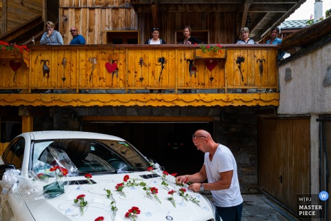 The groom decorates the car in front of the guests on his wedding day in the French Alps.