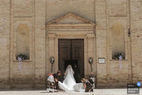 Twee vrouwen helpen de bruid haar prachtige jurk te regelen terwijl ze zich voorbereidt op de ceremonie bij Chiesa Santa Croce Mogliano in deze afbeelding gemaakt door een Macerata, Marche trouwfotograaf.