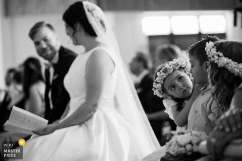 Three little girls aren't paying attention during the ceremony at Vila de Lordelo as the bride sits next to them in this black and white image captured by a Braga, Portugal documentary wedding photographer.