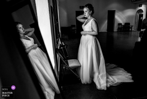 The bride looks at herself in the mirror before the ceremony at Desert Botanical Garden in this black and white award-winning photo composed by a Phoenix, AX wedding photographer.