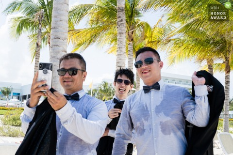 Riu Palace Costa Mujeres Hotel outdoor wedding photography - A hot day shows the Perspiration of the groomsmen under the shade of palm trees.