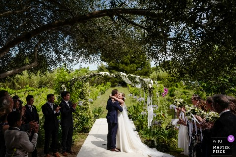 Ceremony kiss under olive tree at the Chateau du Puits es Pratx, Ginestas, FRANCE