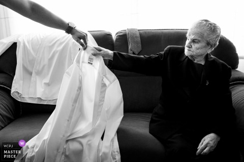A guest hands the groom his shirt while he gets ready before his Albacete wedding in this black and white image composed by a Valencia, Spain wedding photographer.