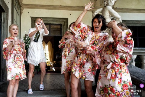 The bride and her bridesmaids celebrate before the ceremony at Palazzo Pfanner in this photo captured by a documentary-style Tuscany wedding photographer.