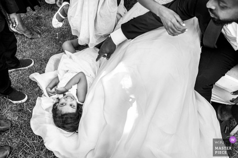 A little girl lays on the bride's train at Addis Ababa in this black and white image created by an award-winning Toronto, Ontario wedding photographer.