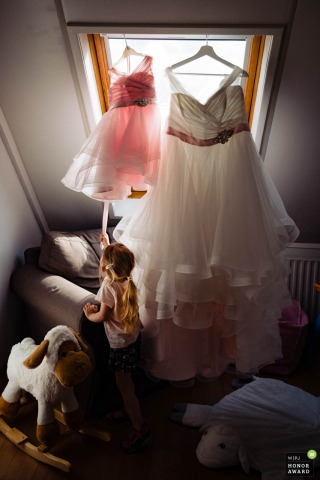 Netherlands - Spijkenisse - Clients home wedding photo of a bridesmaid as she tries to get her dress in between her toys