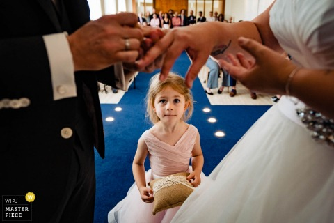 Netherlands wedding ceremony with young daughter watching proudly as her mum and dad give each other wedding rings