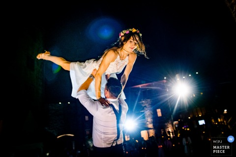 The groom lifts the bride into the air during their first dance at Schloss Romrod in this documentary-style photo created by a Baden-Wurttemberg, Germany wedding photographer.