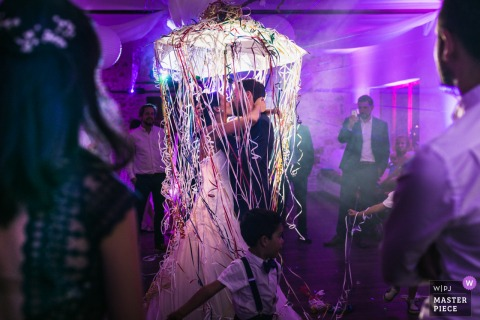 The bride and groom kiss beneath a light covered with long streamers in this photo by a Paris, France wedding photographer.