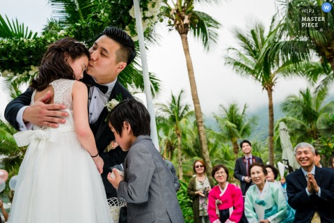 The groom hugs his children during his Da Nang wedding ceremony.