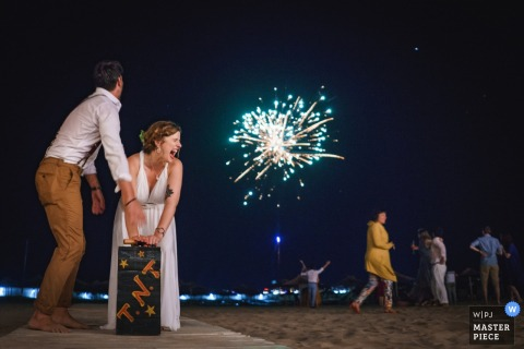 "The bride pushes the lever on a box marked ""T.N.T."" to light a firework at Perla Beach, Primorsko in this wedding image composed by an award-winning Sofia, Bulgaria photographer."