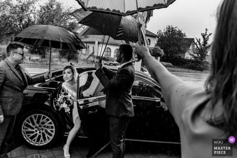 Guests hold umbrellas over the bride as she exits her vehicle at Gemeentehuis Glabbeek in this black and white wedding photo captured by a Flanders, Belgium photographer.