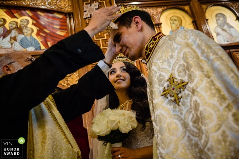 Foto de la ceremonia de boda de la Iglesia Ortodoxa Copta de San Antonio - La novia observa cómo se pone la corona ceremonial en la boda copta.