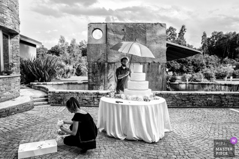 The wedding cake sits ready and waiting at Le Pinete, Viggiù in this black and white photo by an award-winning Milan, Lombardy wedding photographer.