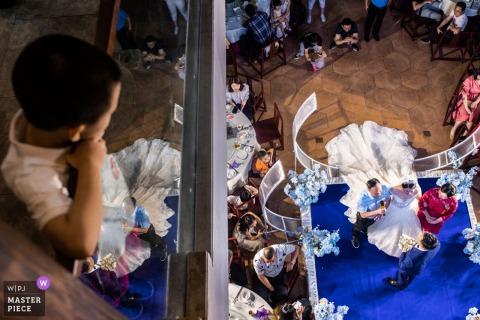 Ein Junge beobachtet die YueYang-Zeremonie von oben auf diesem Foto eines dokumentarischen Hochzeitsfotografen aus Hunan, China.