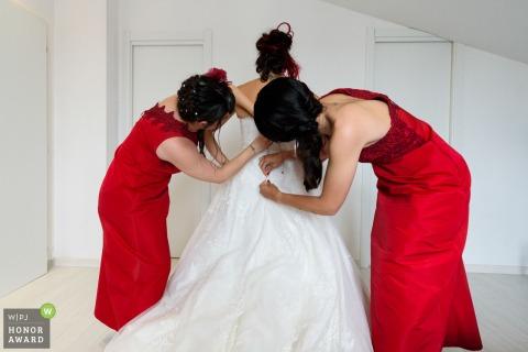 Photo before the ceremony at Santa Maria della Pieve - Arezzo | The bride helped by 2 red bridesmaids