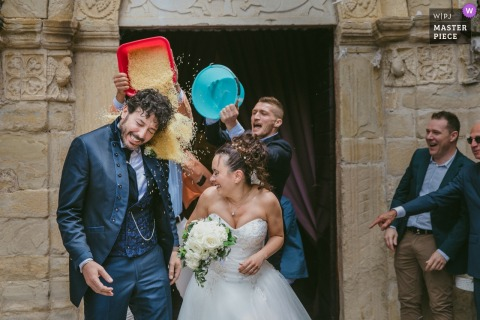 Two guests dump buckets of rice on the bride and groom as they exit their ceremony in this documentary-style wedding photo by a Marche, Italy photographer.