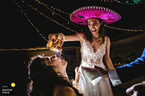 Kınalıada/İstanbul/Turkey wedding photo showing the bride and groom feeding the guests with Mexican tequila
