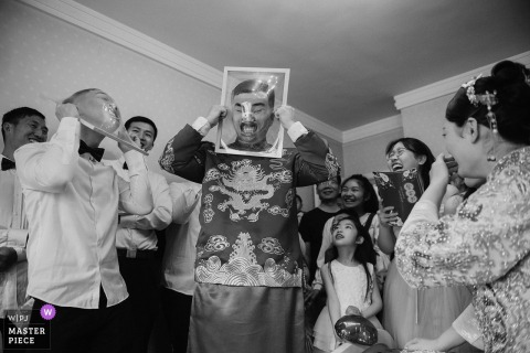 The guests have a game session during this at-home wedding in Xuzhou in this black and white image captured by an award-winning Jiangsu, China wedding photographer.