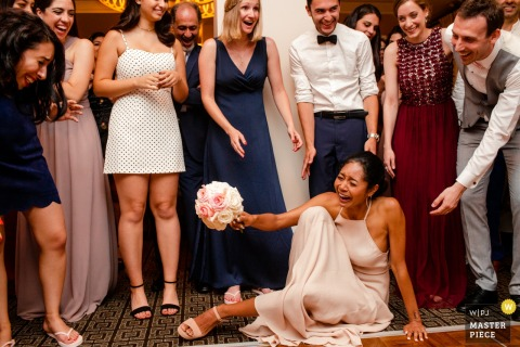 Everyone laughs as a guest tries to stand up after she fell trying to pick up the bouquet at Palo Alto Garden Court Hotel in this wedding image composed by a San Jose, CA photographer.