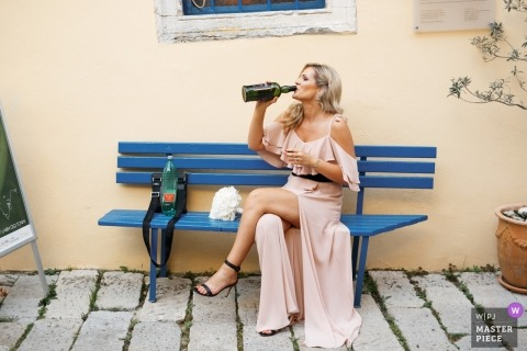 The maid of honor takes a break on a bench in Labin, Istria while she takes a drink from a bottle in this wedding photo composed by an award-winning Croatia photographer.