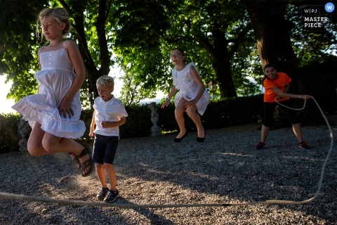 Baronesse Tacco Vinery - Italy Wedding Photographer | Children play in the shade during the aperitif at the winery.