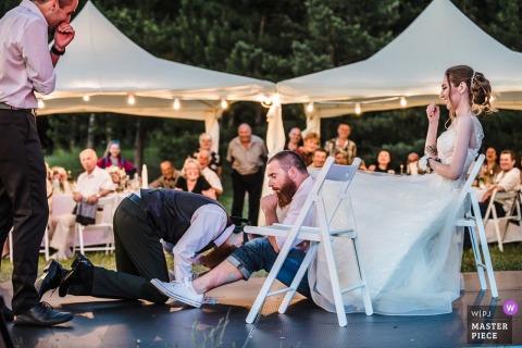 Een man doet zich voor als de bruid als de geblinddoekte bruidegom zijn been raakt in deze foto door een bruiloftsfotograaf in Sofia, Bulgarije.