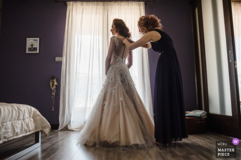 A woman helps the bride close the back of her dress in the final countdown to the ceremony in this award-winning image composed by a Sofia, Bulgaria wedding photographer.