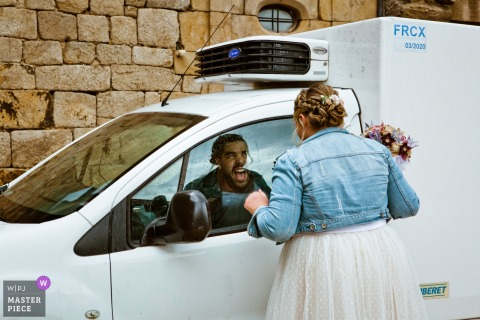 The bride looks at her friend through a car window in Le Cheylard in this wedding image composed by a Drome, Auvergne-Rhone-Alpes photographer.