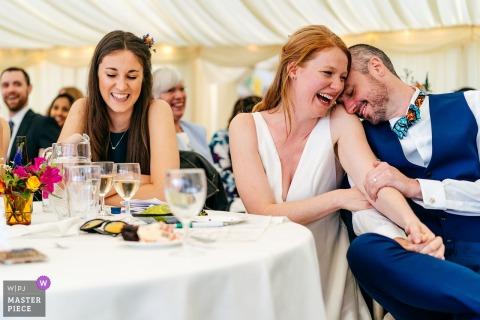 El novio se muere de vergüenza y la novia se ríe mientras el padrino le canta una oda durante sus discursos en Perriswood, Gower, Gales.