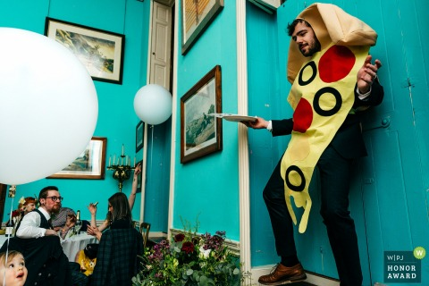 "Walcot Hall Shrewsbury Wedding Photographer: ""Guy dressed as a slice of pizza dances on table top as boy looks on with a look of 'What the hell is going on?!' on his face"""