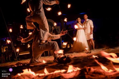 Die Braut, der Bräutigam und die Gäste genießen nachts eine Feuertanzshow in diesem dokumentarischen Hochzeitsbild, das von einem Fotografen in Phuket, Thailand, verfasst wurde.