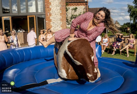 Chaucer Barn, North Norfolk, UK Venue Photography - Wedding guest rides the Rodeo Bull for fun during the evening entertainment.