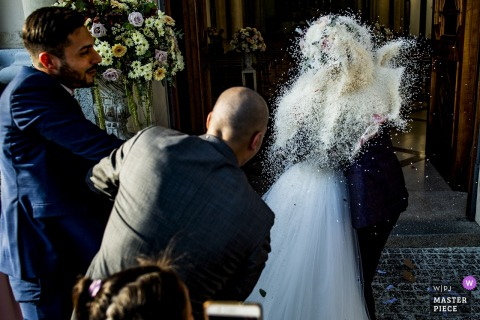 The bride and groom are completely obscured by rice tossed at them by guests as they exit their Reggio Calabria ceremony in this photo by a documentary-style Calabria wedding photographer.