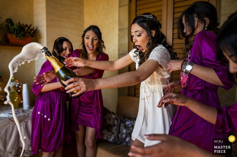 The bride and her bridesmaids are shocked as the bottle of champagne pops open in this award-winning image by a Reggio Calabria, Calabria wedding photographer.