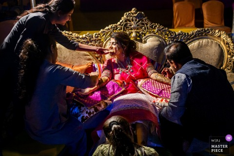 The bride is surrounded by people helping her get ready in Ahmedabad in this photo by a Calabria wedding photographer.