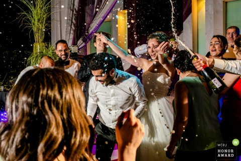 Wyndham Ankara wedding celebration photography   Bride and groom with guests on the dance floor and champagne spraying