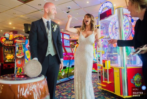 The bride and groom are ready to hit the slot machines at Ocean Kave in this award-winning photo by a Devon, England wedding photographer.